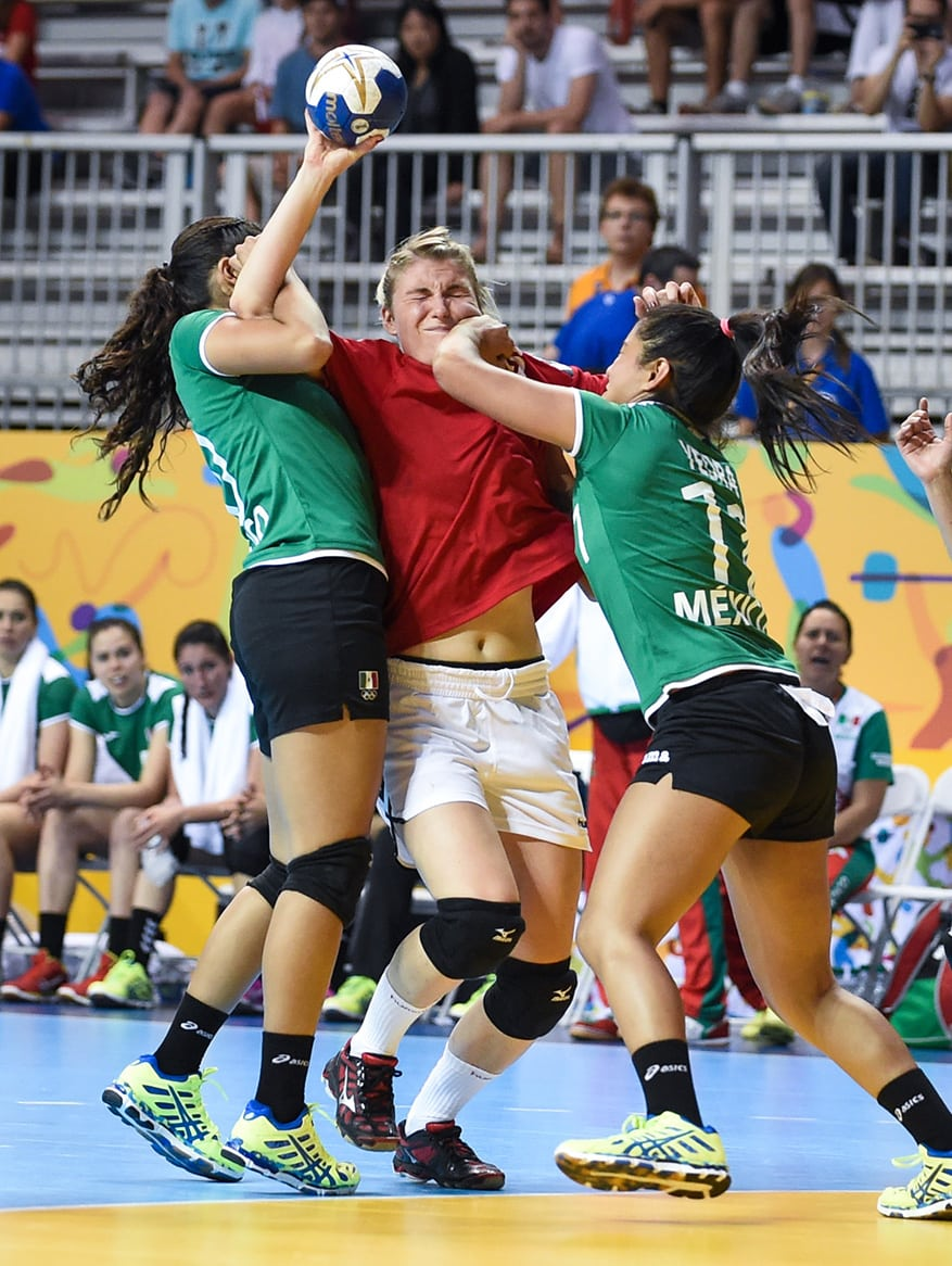Kim Barette of team Canada gets tied up by (left) Fernanda Rivera and (right) Violeta Yedra of team Mexico as part of a preliminary handball game between Canada and Mexico during the Pan Am games in Toronto on Thursday. Mexico won the game 25-22.