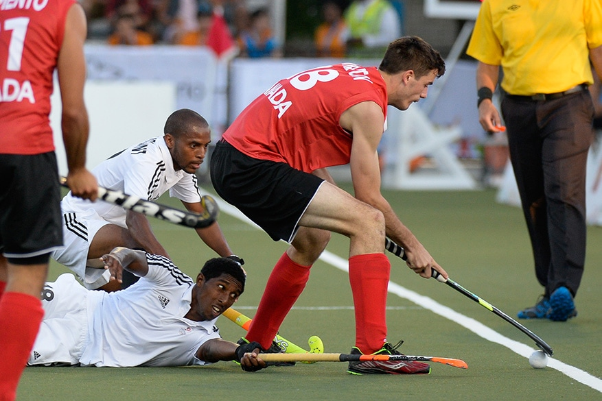 Canada defender Paul Wharton keeps the ball in and away from Trinidad and Tobago midfielders (back) Akim Toussaint and Mickell Pierre during a quarter-final men's field hockey match at the Pan Am Games in Toronto on Tuesday.  Canada won the match 3-1.