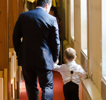 Father holds his son's hand and walks down church isle during a baptism ceremony