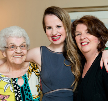 Young teenager stands between her mother and grandmother for a family photo