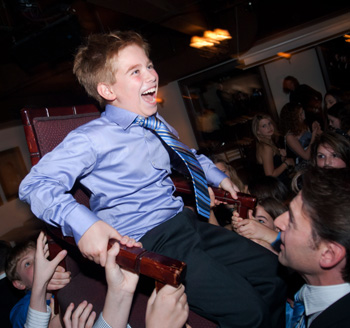 Young man is lifted in the air by family during a Bar Mitzvah celebration