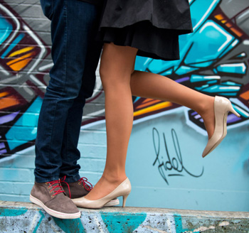 Young trendy couple posing in downtown Toronto in front of a building wall painted with graffiti