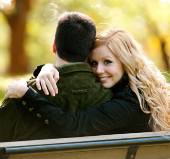 Newly engaged couple pose on a park bench for a fall engagement photo
