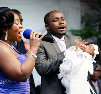African american family celebrates with singing and dancing during baptism celebrations