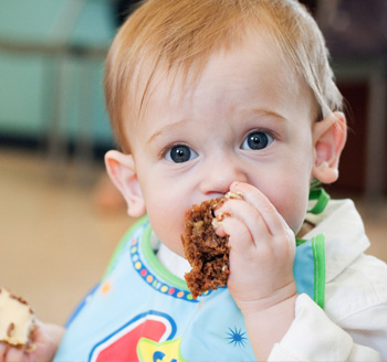 A small baby poses with birthday cake in his mouth during a birthday photo