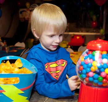 Young boy playing during his birthday party filled with candy and treats