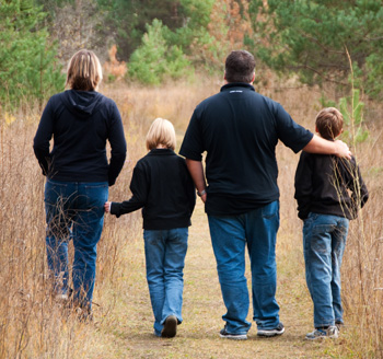 Parents and children go for an autumn walk in a park for a family photo