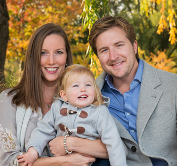 Beautiful young couple holding their toddler during a fall family photo shoot