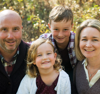 Parents and two young children pose with big smiles for a beautiful family photo
