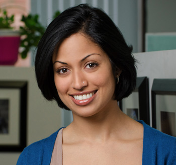 Headshot for young professional woman sitting and smiling in a corporate office