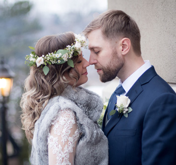 European newlyweds pose for wedding photos wearing floral accents