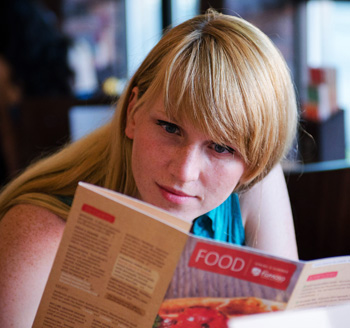 Commercial photo of a restaurant patron browsing the food menu for something to eat