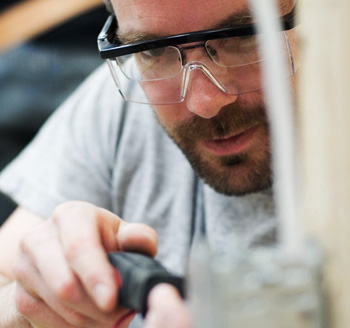 Action shot of tradesman working on the job wearing safety glasses for corporate website