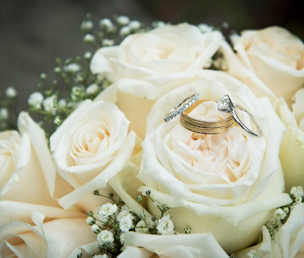 Wedding rings sit on top of a beige wedding bouquet